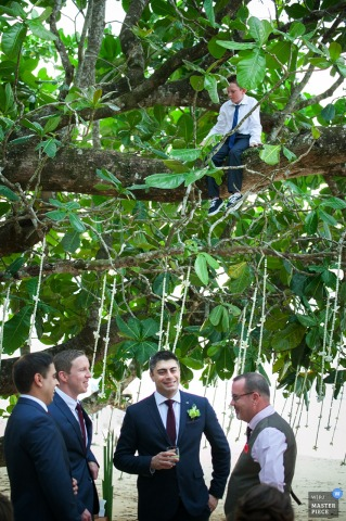 A young boy sits in a tree above the groomsmen in this photo by a Phuket, Thailand wedding photographer.