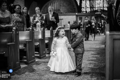 Black and white photo of a young ring bearer helping the flower girl down the aisle by a Washington, D.C. wedding photographer.