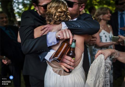 Zwei Männer, die Bier halten, umarmen die Braut, während eine Frau den Zug der Braut in diesem Foto von einem New-Jersey Hochzeitsfotografen hält.