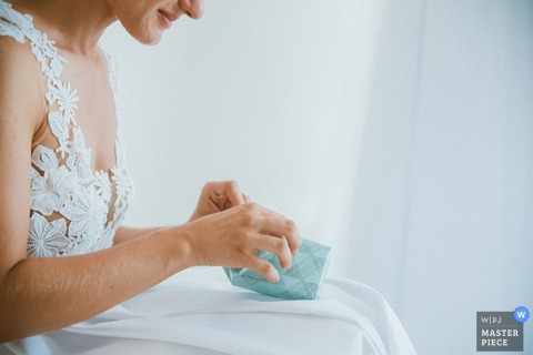 Detail photo of the bride opening a small blue box by a Zurich, Switzerland wedding photographer.