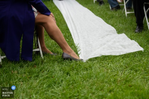 A guest holds down a white carpet with her foot in this detail photo by an Omaha, NE wedding photographer.