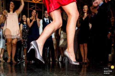 Photo détaillée des talons argentés d'une femme alors qu'elle saute en l'air par un photographe de mariage du New Jersey.