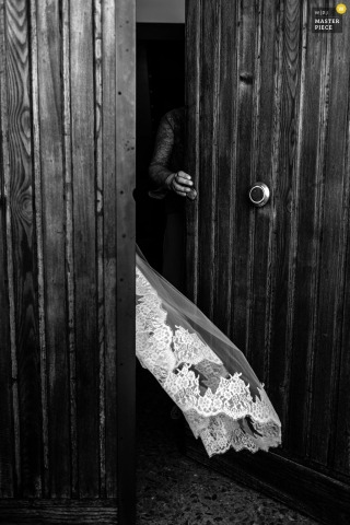 Black and white detail photo of the bride's veil trailing behind her as she disappears behind a door by a Rome wedding photographer.