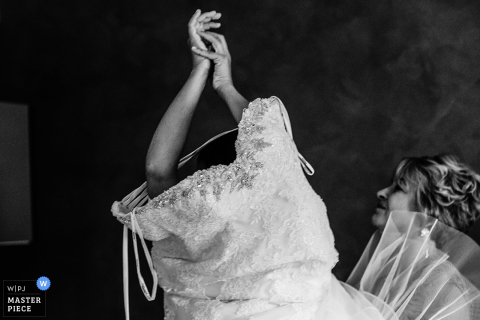 Black and white photo of the bride being helped into her lace wedding gown by a Rome wedding photographer.