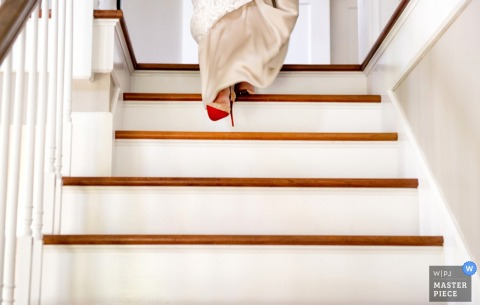 The bride shows off her red shoe as she takes her first step down the stairs in this detail photo by a Houston, TX wedding photographer.
