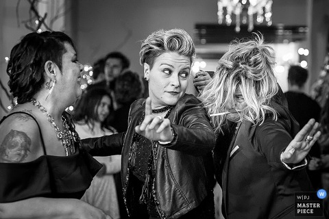 A few guests get ready to party during the reception in this black and white photo by a Tuscany wedding photographer.