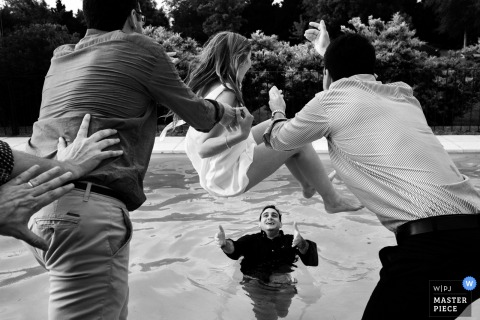 Black and white photo of a young girl being tossed into a pool where a man waits to catch her by a Santa Fe, Argentina wedding photographer.