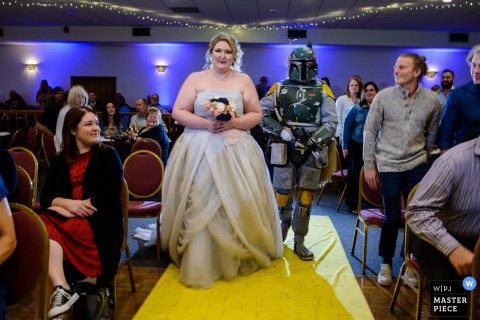 Photo of the bride walking down the aisle alongside a person dressed as Boba Fett by an Omaha, NE wedding photographer.