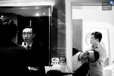 A groomsmen peeks around the corner while another is getting ready in this black and white photo by a China wedding photographer.