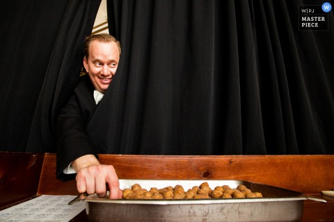 A guest reaches around a black curtain to sneak a bit of food in this photo by a New Jersey wedding photographer.