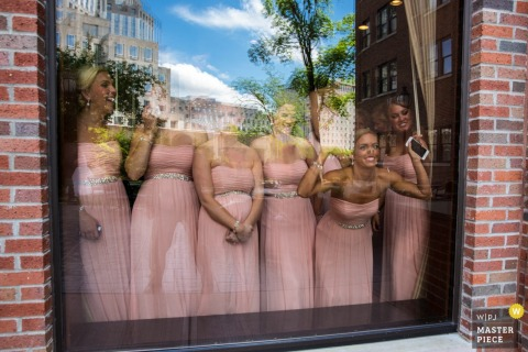 Photo of bridesmaids in their matching, pink dresses looking through a large window by a Cincinnati, OH wedding photographer.