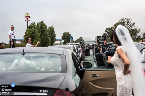 The bride stands outside of her car waiting in traffic in this photo by a Latina, Italy wedding photographer.