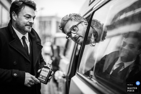 Black and white photo of a man carrying a bottle while another leans his head out of a vehicle to look at it by a London, England wedding reportage photographer.