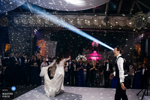 Photo of the bride and groom on the dance floor with a spotlight positioned to look like a beam coming from the groom's eye by a Rome wedding photographer.