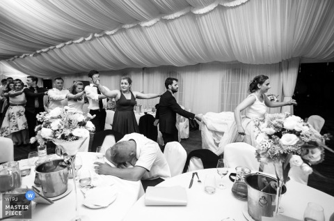 The bride leads a conga line around the reception room while one guest sits out in this black and white photo by a Bytom, Poland wedding photographer.
