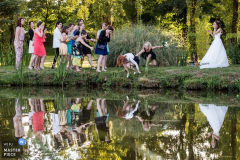 Montpellier wedding photographer captured this humorous photo of wedding guests nearly falling into a pond to catch the brides bouquet
