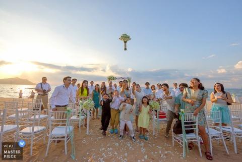 Zdjęcie gości weselnych próbujących złapać bukiet panny młodej, gdy wisi w powietrzu przez fotografa ślubnego z Bangkoku w Tajlandii.