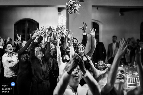Black and white photo of guests reaching up to catch the bride's bouquet by a Tuscany wedding photographer.