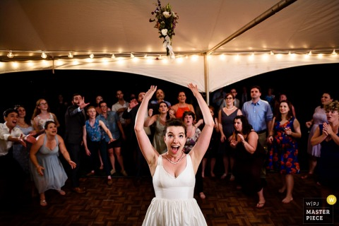 Photo of the bride tossing her bouquet to the guests behind her by a Burlington, VT wedding photographer.