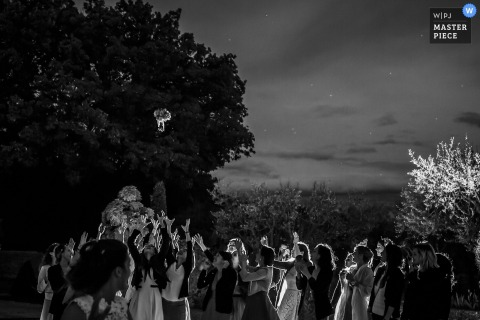 Black and white photo of the bride tossing her bouquet to the guests outside in the evening by a France wedding photographer.