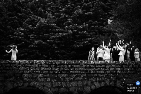 Black and white photo of the bride tossing her bouquet on a stone bridge by a France wedding photographer.