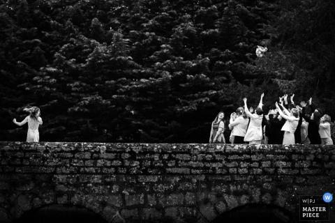 扔她的在一座石橋樑的新娘的黑白照片由法國婚禮攝影師。