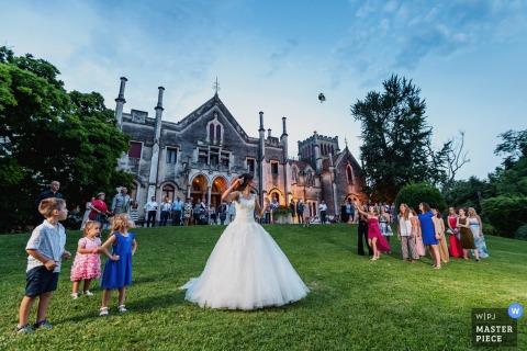 De bruid gooit haar boeket op een groot grasveld voor een statig gebouw op deze foto door een huwelijksfotograaf uit Venetië.