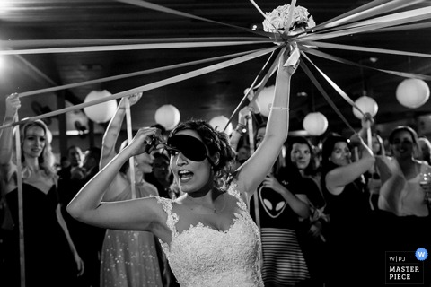 Black and white photo of the bride lifting her blindfold as the women around her carry ribbons tied to her bouquet by a Brazil wedding photographer.