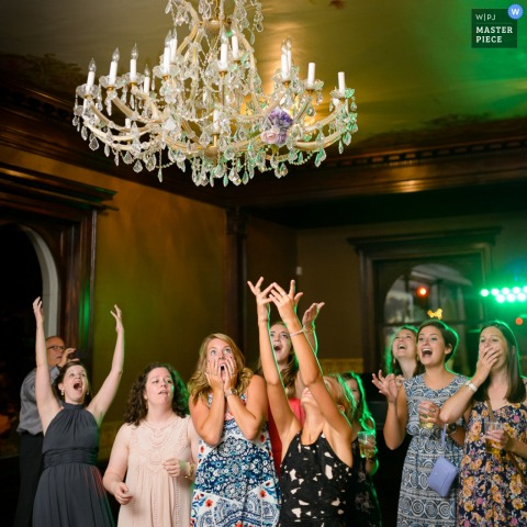 Photo of women hoping to catch the bride's bouquet as it flies through the air by a Minneapolis, MN wedding photographer.
