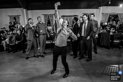 Schwarzweiss-Foto eines Mannes, der das Fangen des Strumpfbandes durch einen Hochzeitsfotografen Charlottes, NC feiert.