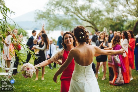 The bride and a guest carrying the bouquet approach each other for a hug in this photo by an Umbria, Italy wedding photographer.