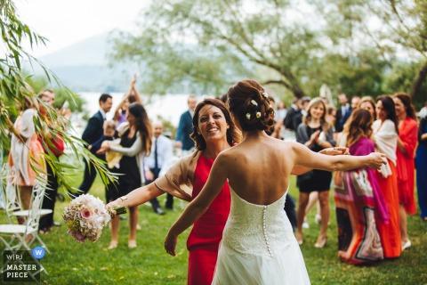 Oblubienica i gość niosący bukiet podchodzą do siebie, aby uścisnąć na tym zdjęciu fotografa ślubnego z Umbrii we Włoszech.