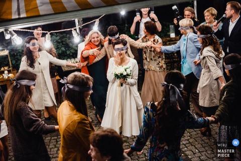 Foto van de bruid en de gasten geblinddoekt als de bruid zich voorbereidt op het gooien van haar boeket door een huwelijksfotograaf in Rusland.