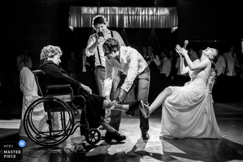 A young man puts the bride's garter on an older woman as the bride laughs in this black and white photo by a Santa Fe, Argentina wedding photographer.
