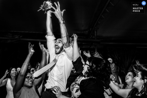 Black and white photo of guests reacting excitedly during the bouquet and garter toss portion of the reception by a Rio de Janeiro, Brazil wedding photographer.