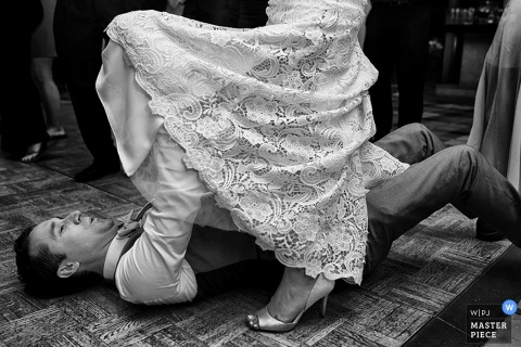 Black and white photo of the groom removing his bride's garter by a Carson City, NV wedding photographer.