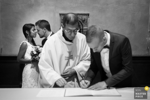 The witness provides his signature for the priest as the bride and groom stand in the background in this black and white photo by a France wedding photographer.