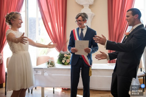The bride and groom reach out to each other during the ceremony in this photo by a France wedding photographer.