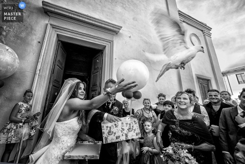 The bride releases a white dove after the ceremony as guests watch in this black and white photo by a Tuscany wedding photographer.