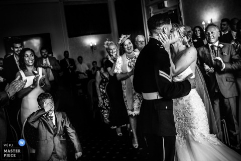 Zwart-witfoto van de gasten die applaudisseren terwijl de bruidegom de bruid kust tijdens de ceremonie door een fotograaf uit de huwelijksreportage van Devon, Engeland.