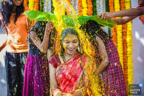 Dwie dziewczyny trzymają duży liść ochronny, gdy na zdjęcie wylewa się żółty płyn na pannę młodą na zdjęciu autorstwa fotografa ślubnego z Indii.