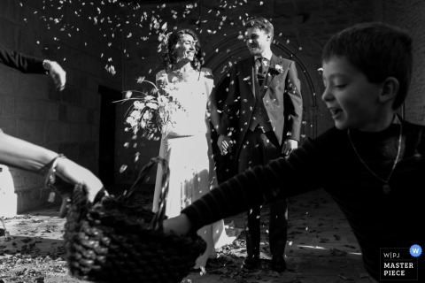 Black and white photo of a young boy reaching into a basket for flower petals as guests toss them towards the bride and groom by a France wedding photographer.