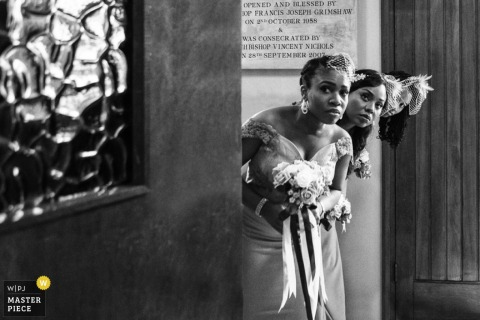 Black and white photo of the bride and two bridesmaids peeking around a corner by a London, England wedding reportage photographer.