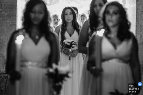 Schwarzweiss-Foto der Braut, die sich vorbereitet, den Gang hinunter zu gehen, während ihre Brautjungfern ihr von einem Hochzeitsfotografen Lissabons, Portugal vorangehen.