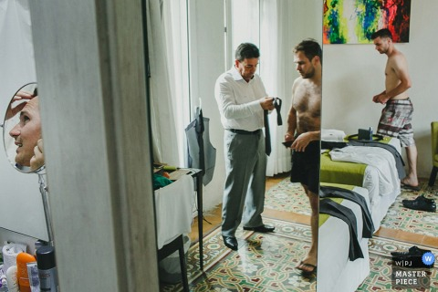 Photo of men getting ready before the ceremony reflected in a large mirror by a Brazil wedding photographer.