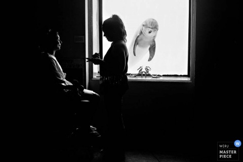 The bride is silhouetted as she gets her makeup done in front of a dolphin in this black and white photo by a Jacksonville, FL wedding photographer.