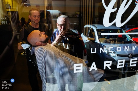 Photo of a man reflected in a window watching another man in the barber shop by a Rome wedding photographer.