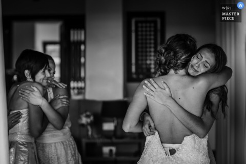 A woman hugs the bride as two other girls hug each other in this black and white photo by a France wedding photographer.