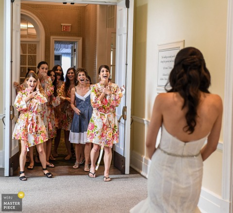 Photo of the bridesmaids reacting to the bride in her gown as they stand in their robes by a Los Angeles, CA wedding photographer.