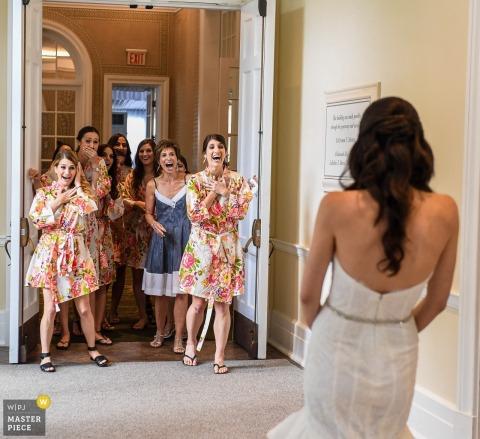 Foto van de bruidsmeisjes die op de bruid in haar toga reageren aangezien zij zich in hun robes door een het huwelijksfotograaf van Los Angeles, CA bevinden.